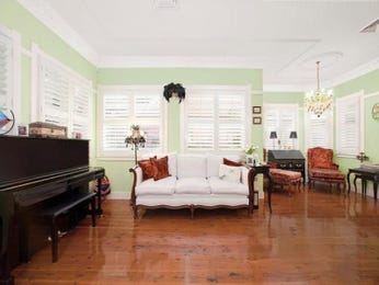Open plan living room using green colours with floorboards & louvre windows - Living Area photo 172946