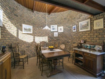 Country dining room idea with exposed brick & exposed eaves - Dining Room Photo 8964201