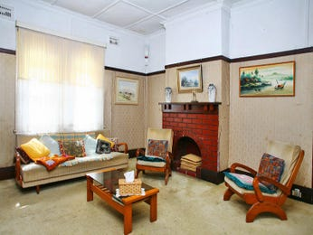 Open plan living room using brown colours with hardwood & bay windows - Living Area photo 388284