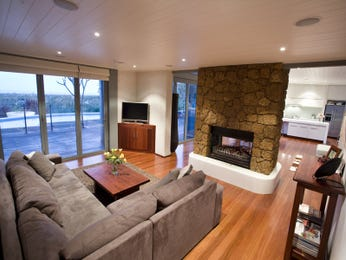 Open plan living room using brown colours with floorboards & fireplace - Living Area photo 297128