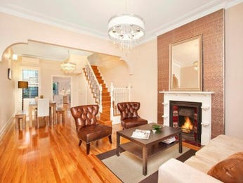 Dining-living living room using brown colours with floorboards & fireplace - Living Area photo 1382416