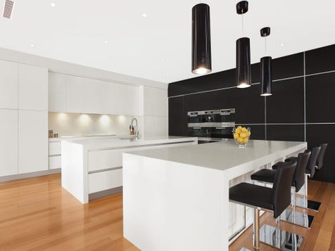 "FUNCTIONAL FUSION This kitchen features white gloss cupboards with a black gloss feature wall.  2 x huge islands with all drawers on both sides.  There is enough space to entertain a party.  This kitchen was featured in the ""My Kitchen Rules"" commercial with all the celebrities, due to the size and unusual design.  The kitchen has 2 x Miele Fridge integrations, induction, inbuilt range hood, and integrated dishwasher. Splash back is ""Star Fire White"""
