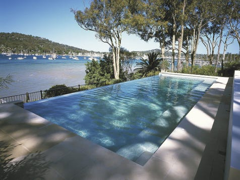 INFINITY EDGED SWIMMING POOLS Once reserved for exotic resorts, high-end luxury homes and glossy magazines, infinity-edge swimming pools have now become a popular option for average Aussie homeowners looking to add a bit of luxury to their backyards. An infinity-edge swimming pool blends seamlessly with the horizon beyond, creating a dramatic impact to your backyard pool. Also known as the negative-edge pool, an infinity pool features one or more sides over which the water cascades giving the appearance it is merging with the horizon beyond. Infinity pools provide an even bigger visual impact when they are built in a backyard overlooking a harbour, lake or ocean, but locations set on a hill or in the country deliver as equally incredible views.