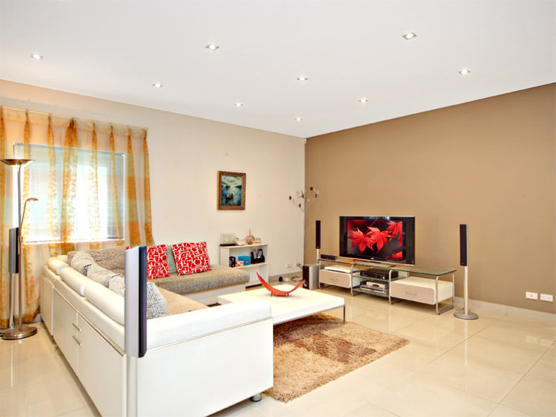 Open plan living room using brown colours with stone Fireplace feature wall colour