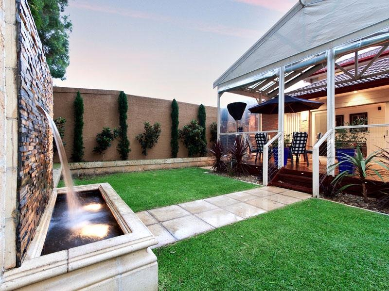 Modern garden design using grass with deck fountain for Asadores para jardin modernos