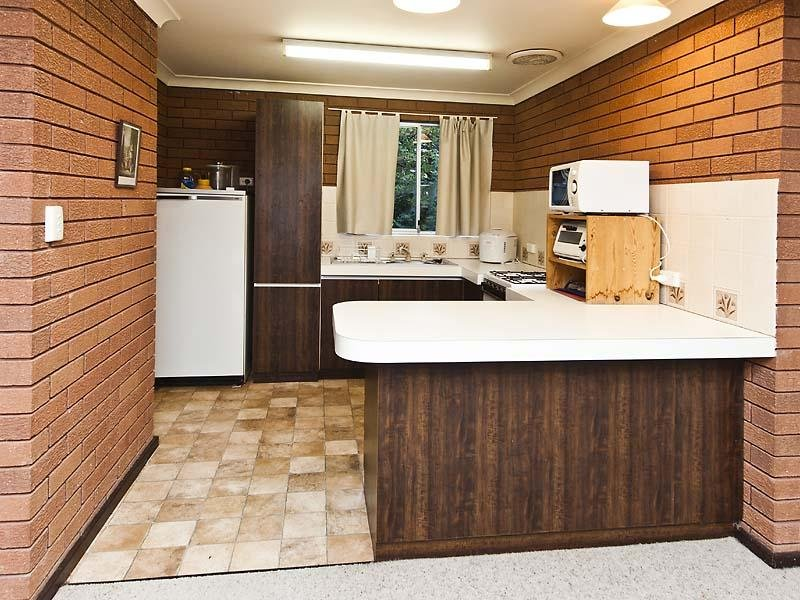 Country u shaped kitchen design using exposed brick for Kitchen designs with exposed brick