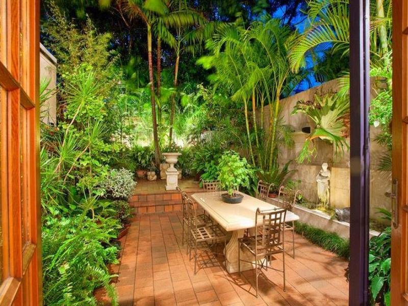 Landscaped garden design using tiles with outdoor dining for Tropical courtyard garden design
